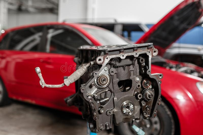 Selective focus. Engine Block on a repair stand with Piston and Connecting Rod of Automotive technology. Blurred red car stock photography