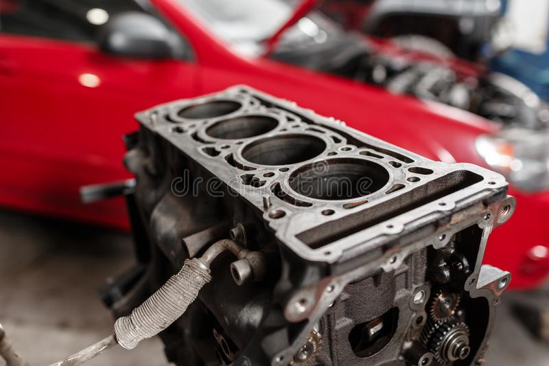 Selective focus. Engine Block on a repair stand with Piston and Connecting Rod of Automotive technology. Blurred red car stock images