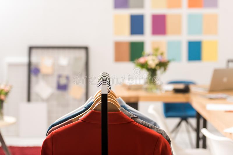 Selective focus of fashionable clothes on hangers. In modern office royalty free stock images