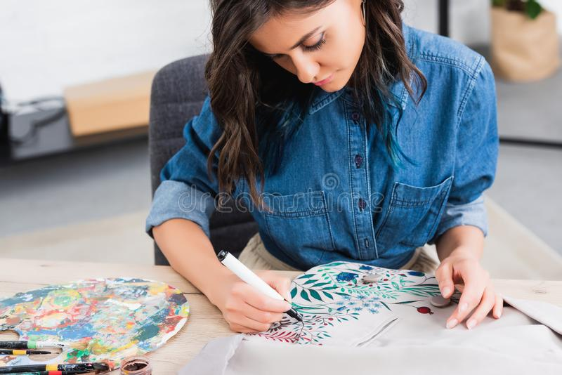 Selective focus of female fashion designer painting on jacket at working table in clothing. Design studio royalty free stock image