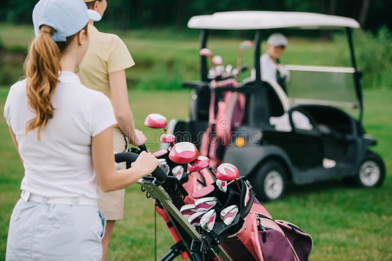 selective focus of female golf players with golf equipment and friend in golf cart behind stock photography