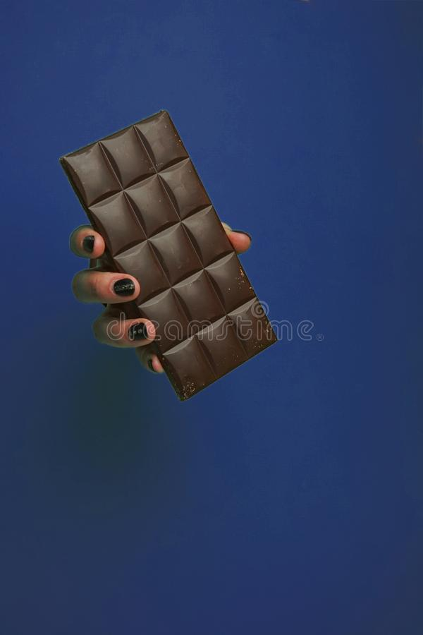 Female hand in a circular hole in the blue trend background. Selective focus, a female hand in a round hole, in the background, holding a dark chocolate bar stock photos