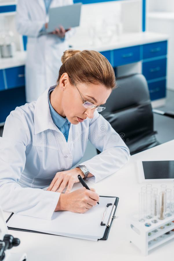 Selective focus of female scientist making notes in notepad with colleague behind. In lab stock photography