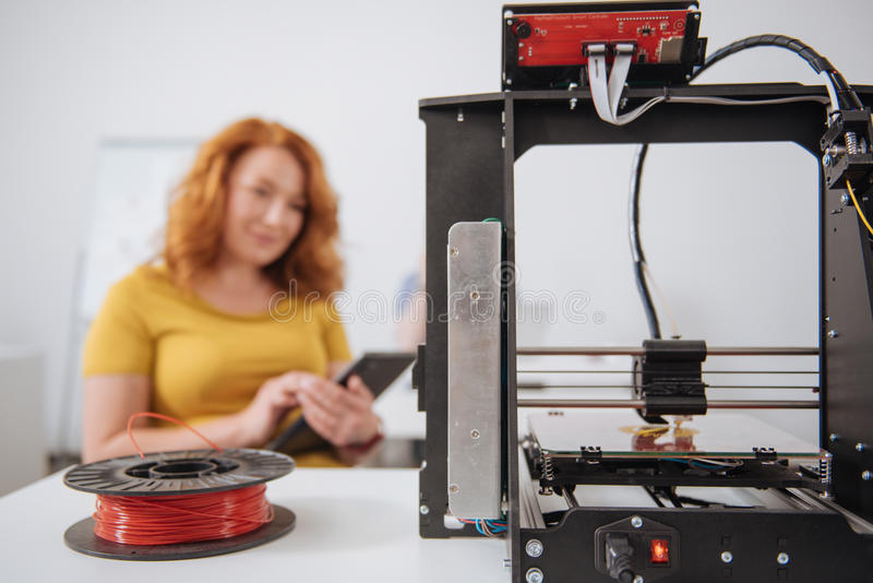 Selective focus of a filament lying near the 3d printer. 3d printing equipment. Selective focus of a filament lying near the 3d printer while being ready for stock image
