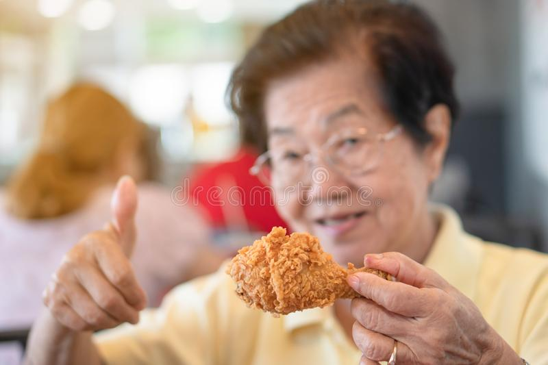 Selective focus of fried chicken, Asian elderly women are eating fried chicken. In the restaurant, lift the thumb. Concept of agin royalty free stock images