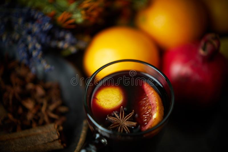 Selective focus on glass mug with mulled wine. On top of vine surface star anise and slice of orange. Soft focus on background stock image
