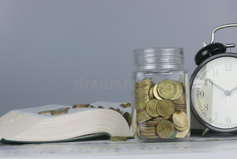 Selective focus of Gold coins on book with clock. Finance and education concept. Money, university, college, school, student, investment, study, savings, bank stock photography