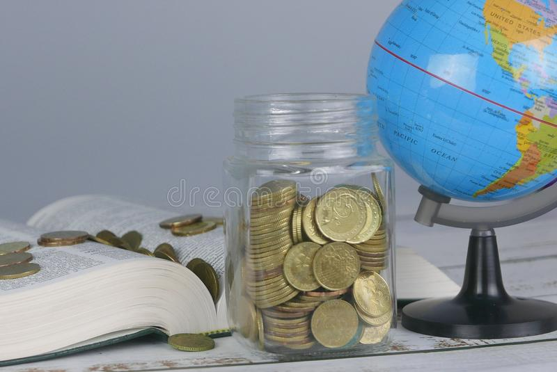 Selective focus of Gold coins on book with globe. Finance and education concept. Money, university, college, school, student, investment, study, savings, bank royalty free stock photo