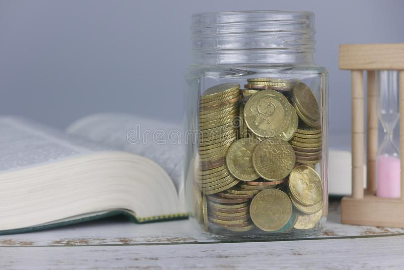 Selective focus of Gold coins on book with hourglass. Finance and education concept. Money, university, college, school, student, investment, study, savings royalty free stock photos