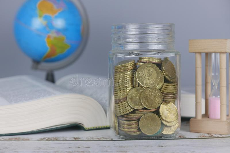 Selective focus of Gold coins, book, hourglass and globe. Finance and education concept. Money, university, college, school, student, investment, study stock photo