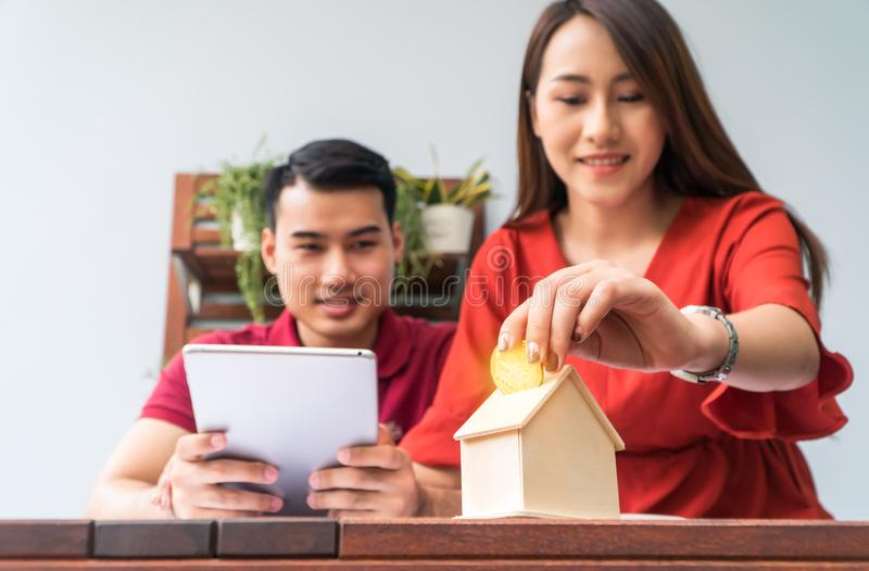 Selective focus of golden coin. Happy Asian couples smiling Because it is profitable from investment And have savings for buying a stock photography