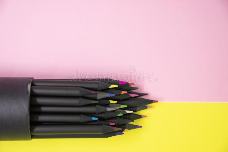 Selective focus of group of black colourful pencil on bright yellow and pink background with copy space. Colourful bright beauty concept stock photos