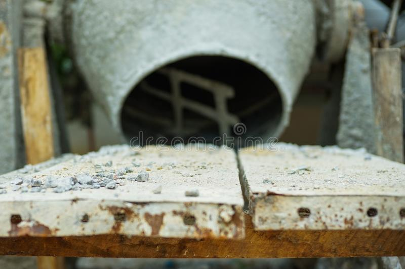 Selective focus on group of crashed stones on the steel plate with blurred concrete mixer. At construction site royalty free stock photos