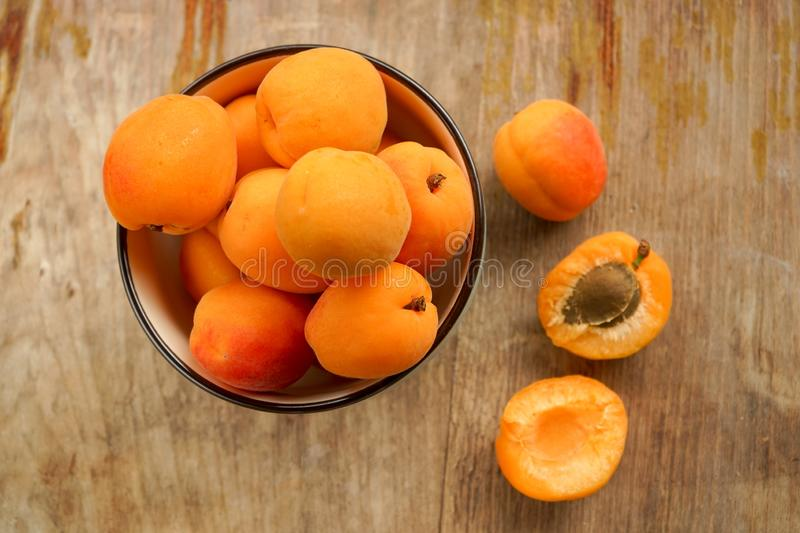 Juicy delicious apricot halves with bone and full ceramic more often whole PP. Selective focus, halves of apricots with seeds from whole fruits on a dark stock images