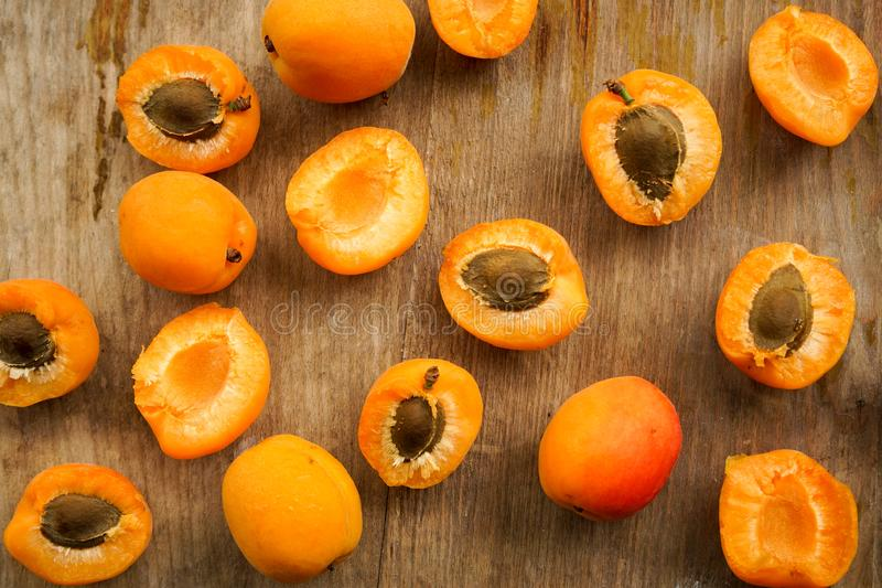 Juicy delicious apricot halves with bone. Selective focus, halves of apricots with seeds from whole fruits on a dark textured wooden Board stock images