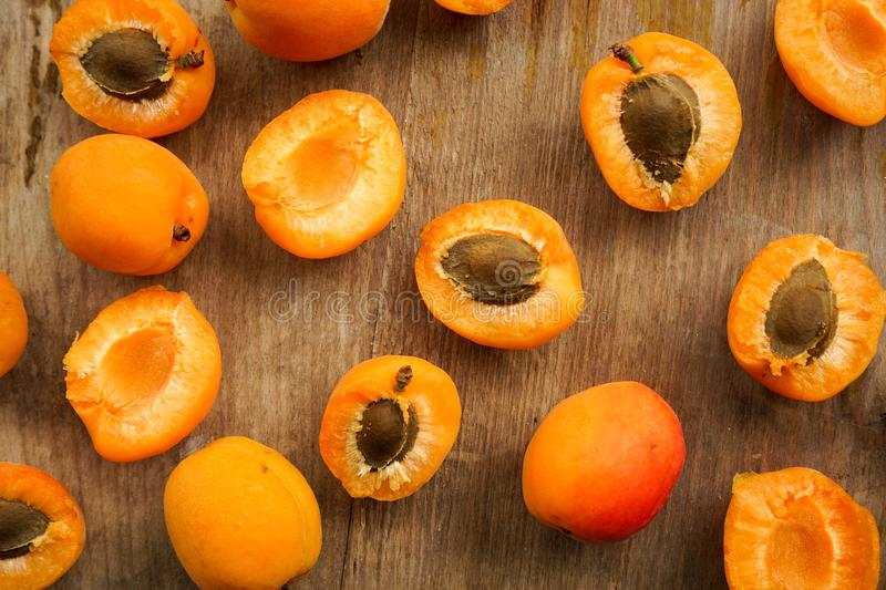 Juicy delicious apricot halves with bone. Selective focus, halves of apricots with seeds from whole fruits on a dark textured wooden Board stock image