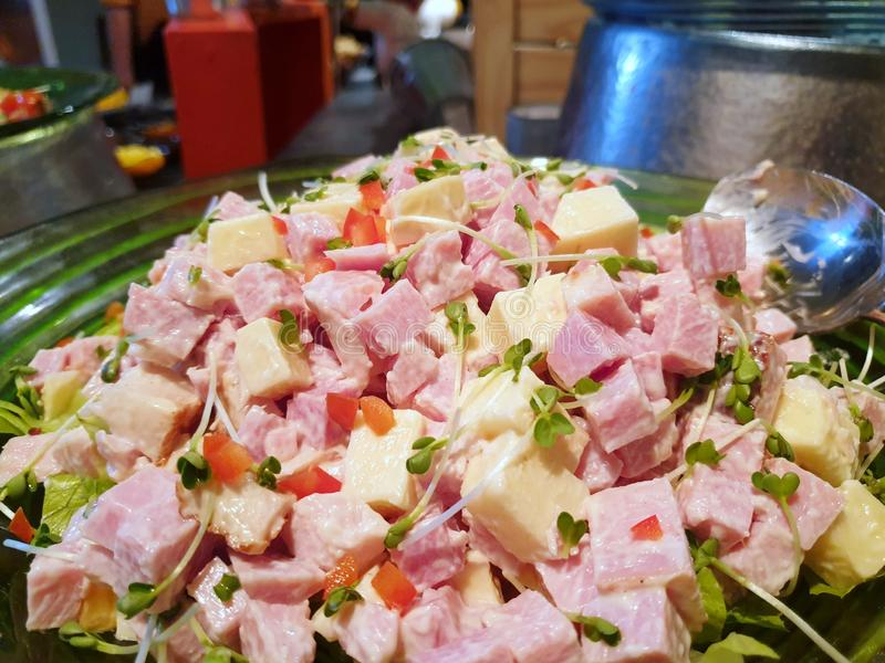Selective focus of ham sausage salad with tomato, onion, sunflower seedlings and mayonnaise on plate in restaurant stock photography