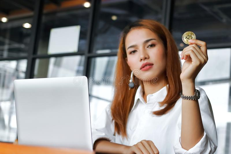 Selective focus on hand of Asian business woman holding cryptocurrency golden bitcoin coin in office. Virtual money on digital. stock photography