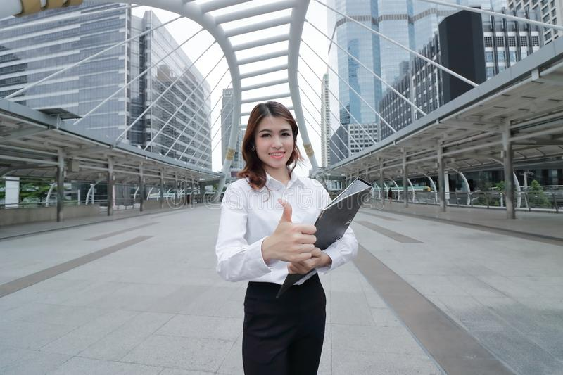 Selective focus on hand of cheerful young Asian businesswoman looking confident and showing thump up sign in the city background. royalty free stock images