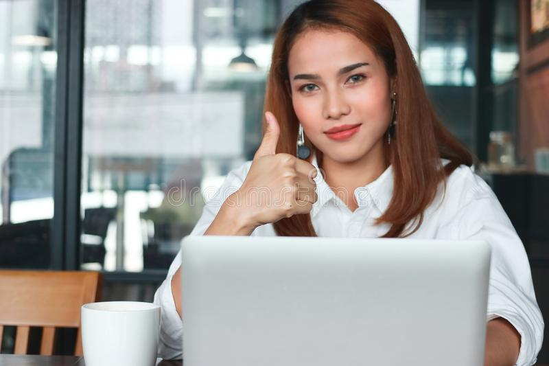 Selective focus on hands of confident young Asian business woman shows thumbs up hands sign in office. stock photos
