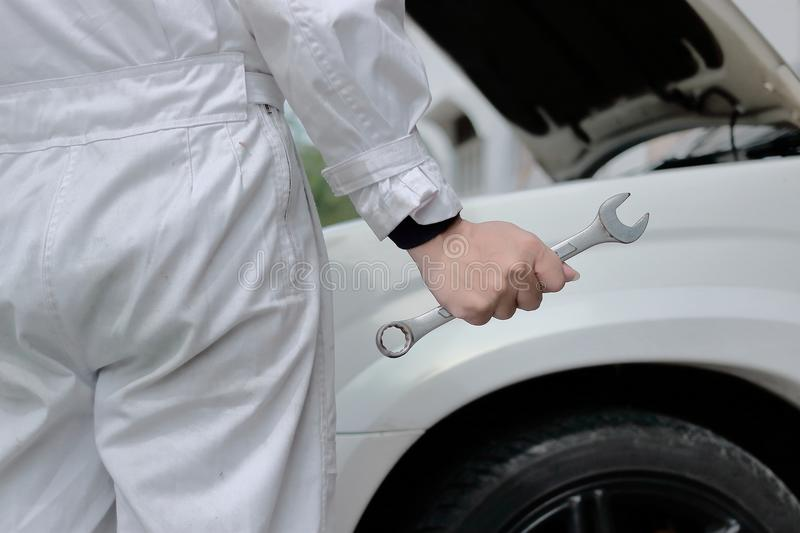 Selective focus on hands of professional mechanic man holding wrench with car in open hood at the repair garage background. royalty free stock photo