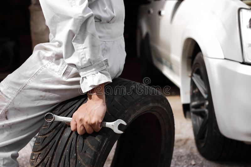 Selective focus on hands of professional mechanic in uniform holding wrench and tire at the repair garage background. Insurance ca. R concept royalty free stock image