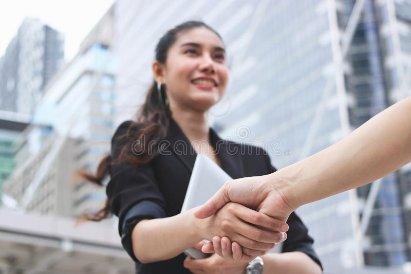 Selective focus on hands of success young Asian business woman and man shaking hands after deal. Partnership concept.  royalty free stock images