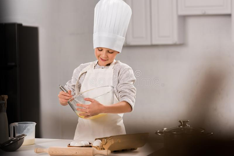Selective focus of happy boy in chef hat and apron whisking eggs in bowl at table. In kitchen royalty free stock photo