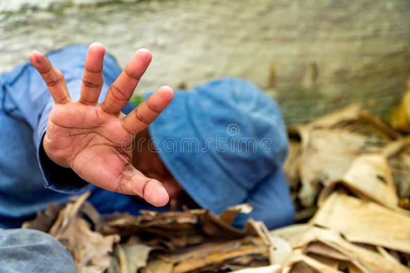 Selective focus of Homeless dirty hand in abandoned house. Him He tried to raise his hand to prevent danger from physical abuse. c royalty free stock photos
