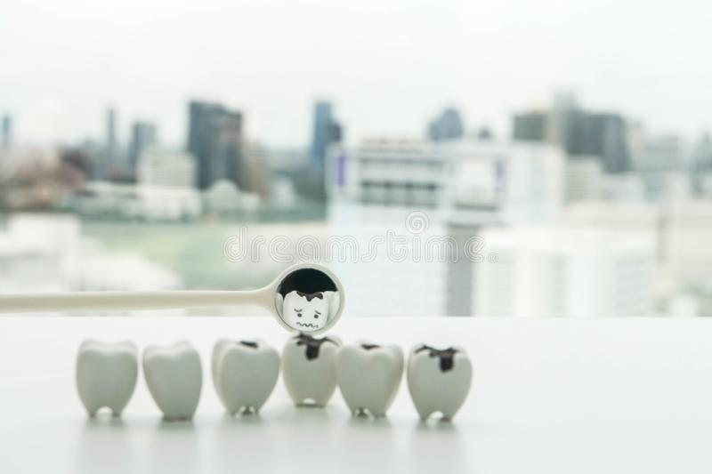 Selective focus icon of decay tooth from dental mirror for human oral health royalty free stock images