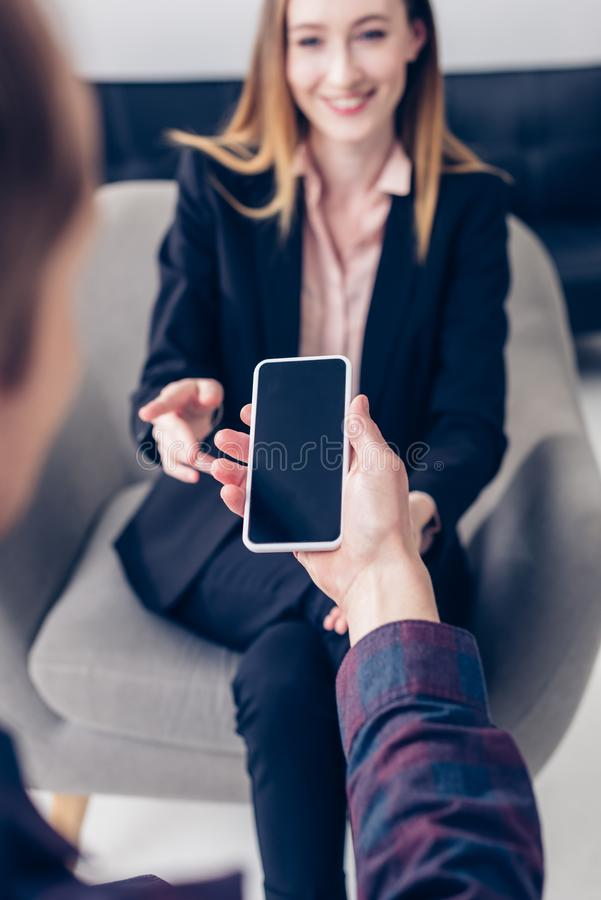 Selective focus of journalist recording interview with businesswoman on smartphone. In office royalty free stock photo