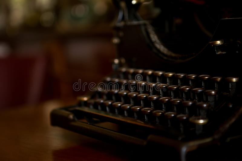 Selective focus on the keyboard key on an old black rustic typewriter on a desk in the office. The typewriter is a lot old so the royalty free stock photography