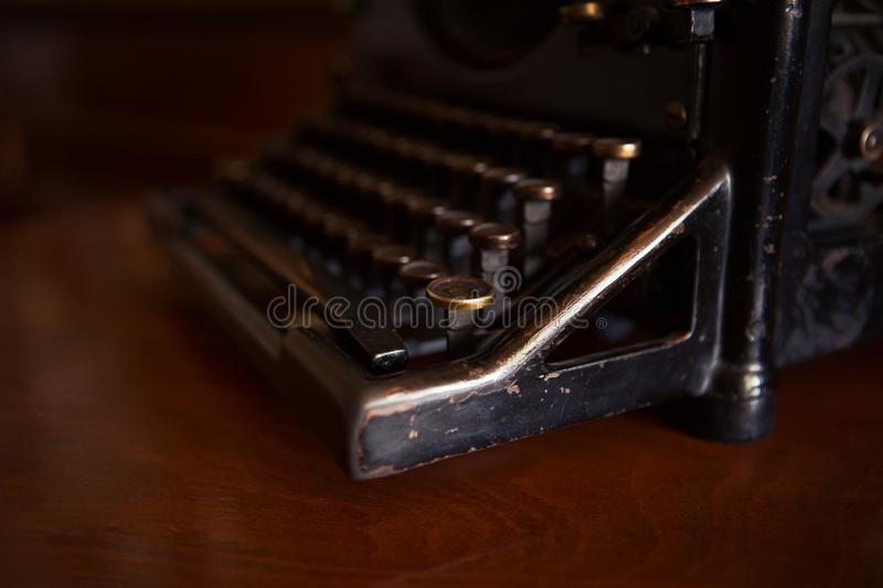 Selective focus on the keyboard key on an old black rustic typewriter on a desk in the office. The typewriter is much used but is stock photos
