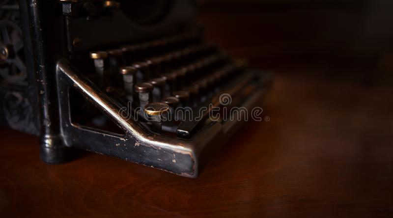 Selective focus on the keyboard key on an old black rustic typewriter on a desk in the office. The typewriter is much used but is stock image