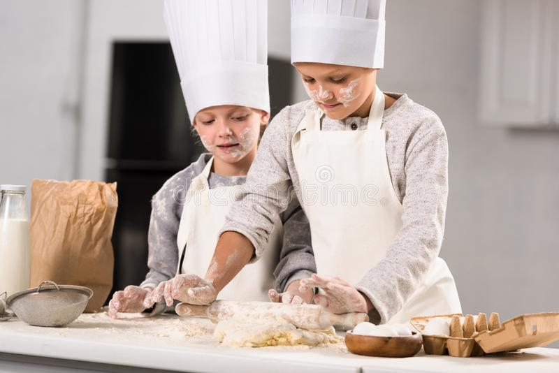 Selective focus of kids in aprons and chef hats making dough with rolling pin at table. In kitchen royalty free stock photos