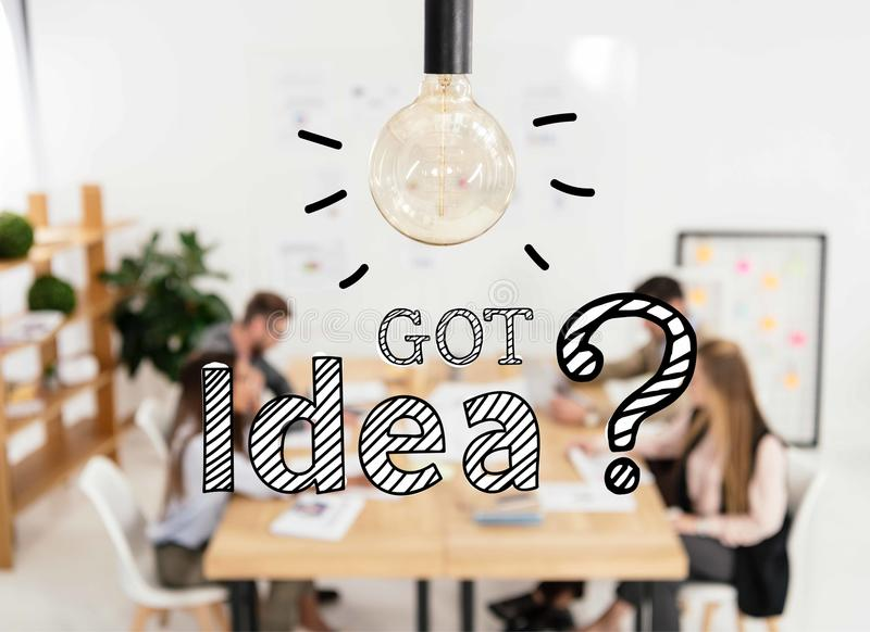 Selective focus of light bulb and multicultural group of marketing managers working in office, got idea. Question signs royalty free illustration