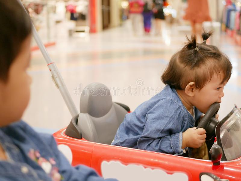 Little Asian baby girl, 17 months old, right biting a steering wheel of a mini car - toddlers and biting. Selective focus of little Asian baby girl, 17 months royalty free stock image