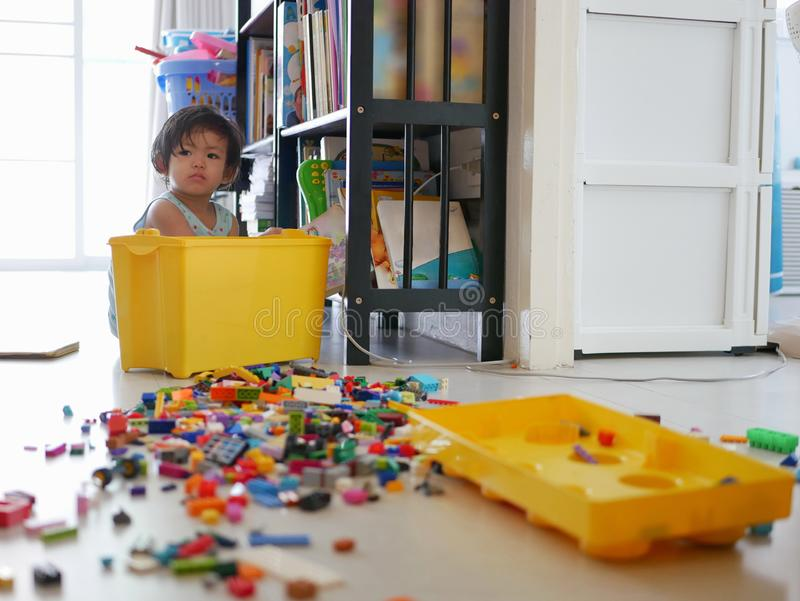 Selective focus of a little Asian baby girl searching a box of toys and spreding them all over the floor royalty free stock images