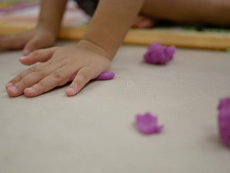 Little baby`s hands playing play dough on the floor stock photography