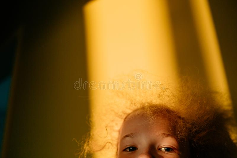 Selective focus. The little blonde cute girl plays hide and seek. Sunset warm light. Sunlight in hair. Summer happy time. Indoor stock image