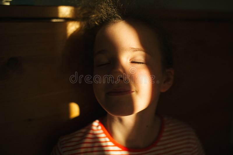 Selective focus. The little blonde cute girl smiles with closed eyes. Sunset warm light. Sunlight in hair. Summer happy time. Indoor stock image