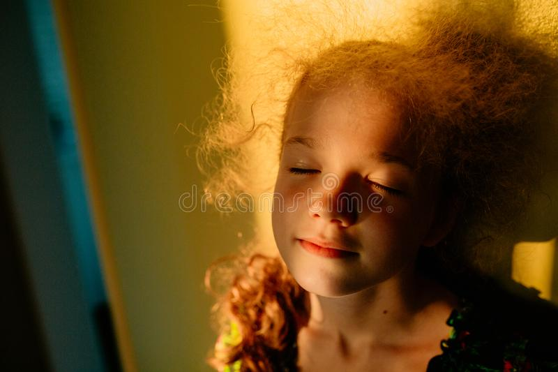Selective focus. The little blonde cute girl smiles with closed eyes. Sunset warm light. Sunlight in hair. Summer happy time. Indoor stock photos