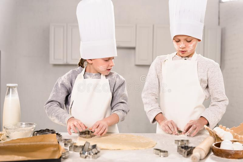Selective focus of little brother and sister in chef hats and aprons cutting out dough for cookies at table. In kitchen royalty free stock image