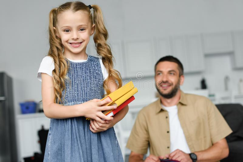 selective focus of little kid with books and father behind at home back to royalty free stock image