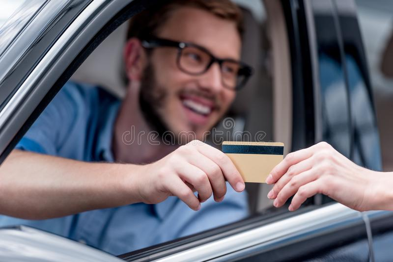 Selective focus of man paying with credit card while. Driving car stock photos