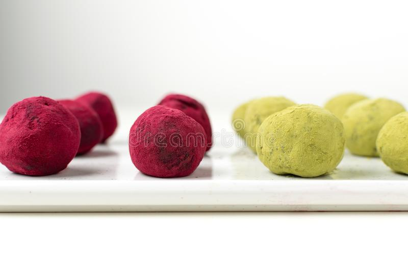 Selective focus on matcha green tea and pink raspberry beetroot truffles stock photo