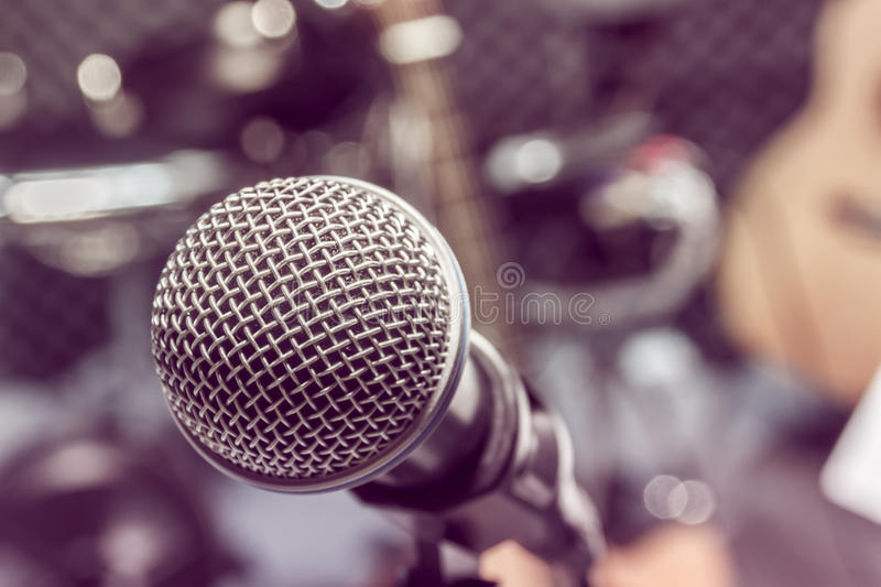 Selective focus microphone and blur musical equipment guitar ,bass, drum lyric stand, background. The selective focus microphone and blur musical equipment royalty free stock image