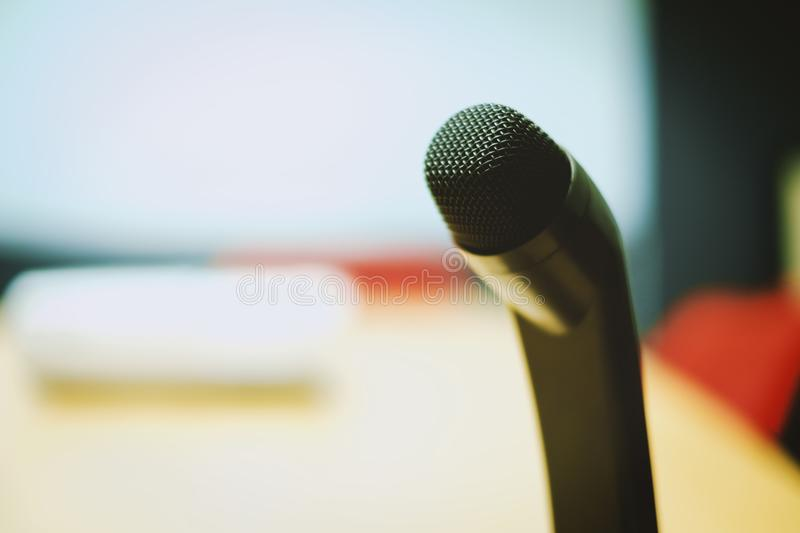 Selective focus of microphone on blurred conference room background stock photo