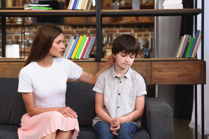 Selective focus of mother cheering up depressed little son on sofa. At home royalty free stock images