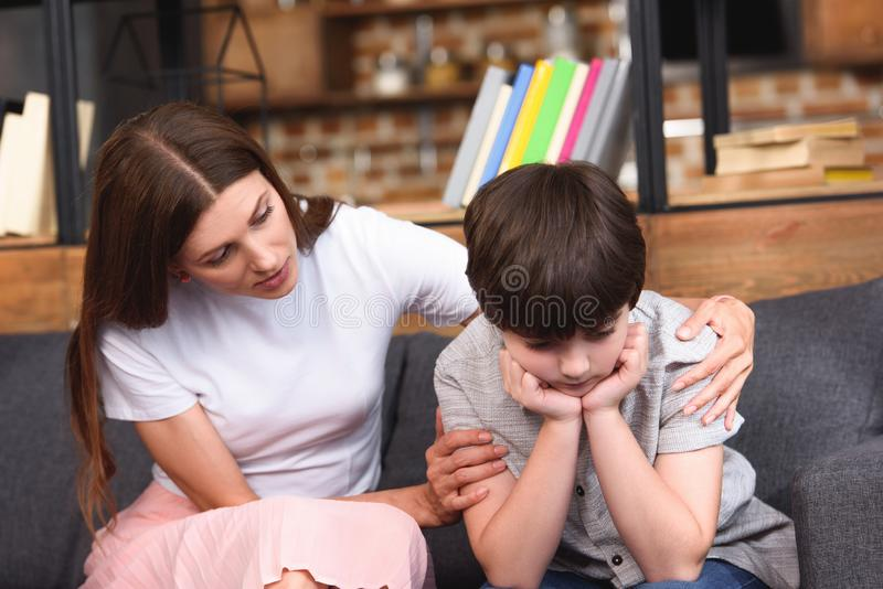 Selective focus of mother cheering up depressed little son on sofa. At home royalty free stock photo